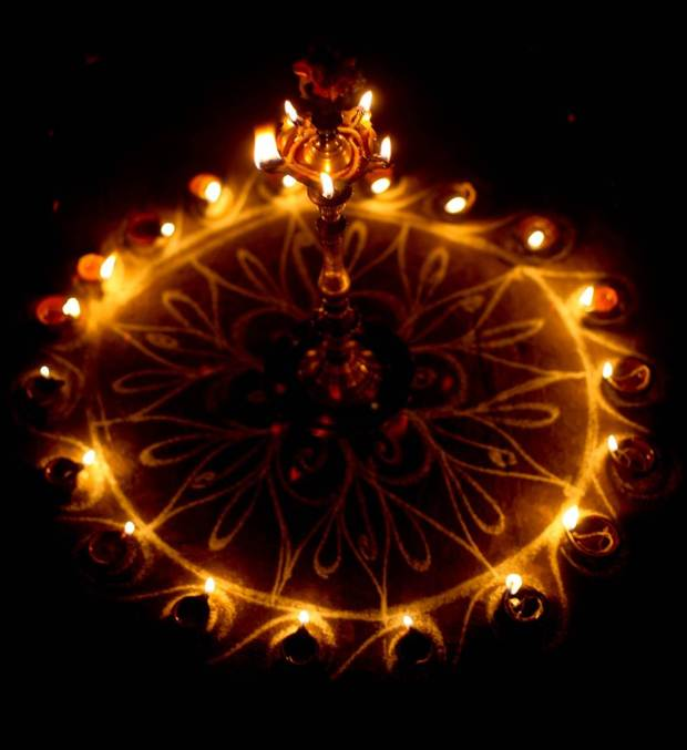 This image shows a kolam decked out with tiny lamps. Women all over Tamil Nadu create kolams outside their homes every morning, they are thought to bestow prosperity to homes. Drawn on the ground with white rice powder or chalk powder the drawings usually get walked on, rained out, or blown away by the wind but during Karthikai Deepam they were preserved and then embellished.
