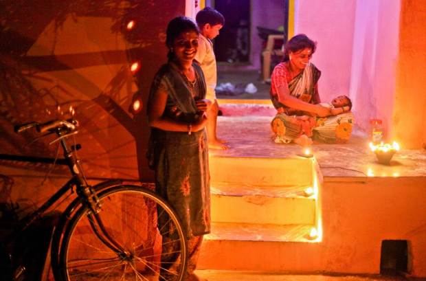 Families sat in front of their homes smile easily at passers-by and offer them good fortune on this auspicious day. The soft glow cast by the metal ghee lamps creates a warm and inviting tone to the streets of Thanjavur in Tamil Nadu.