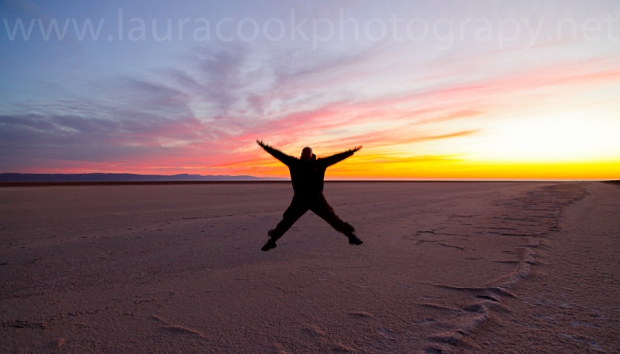 My husband leaps for the sky as the sun rises the next day over the salt flats of Chott El Jerid