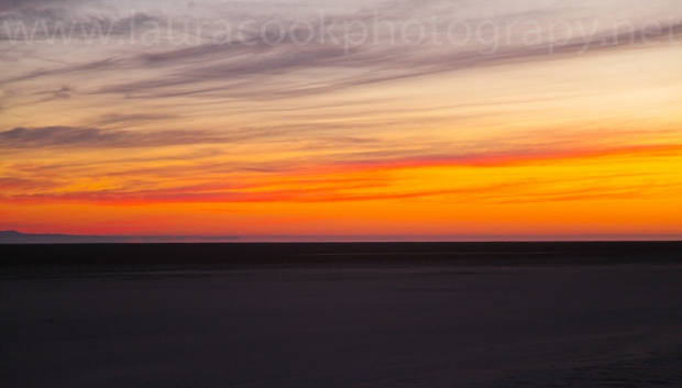 The salt flats provide a blank canvas as the sun begins to warm up the sky.