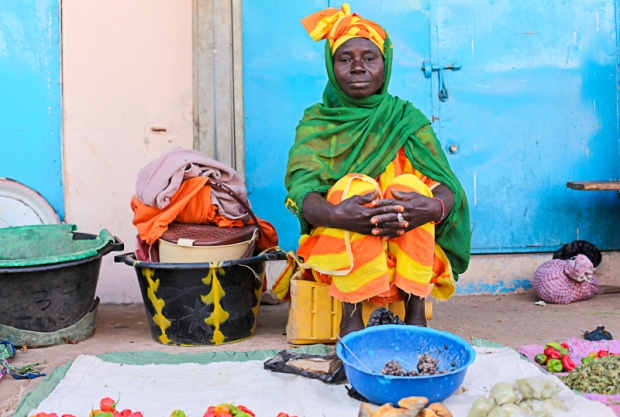 The bright colours of the fruit and vegetables matched only by the bright colours of the women's clothes.