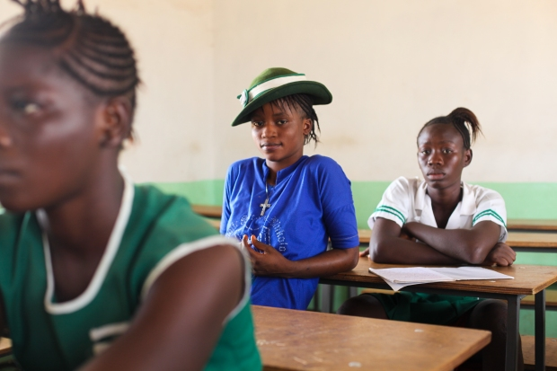 "Rabiatu sits in class learning about verbs (Makeni, Sierra Leone). Nearly just as many girls as boys start secondary school in Sierra Leone but many drop out before they reach Rabiatu's age. Staying in school gives young girls many more options though and as Rabiatu said, ""with education I can be whoever I want to be."""