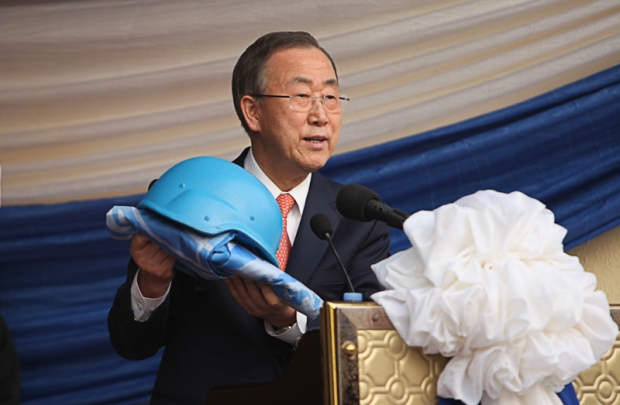 The symbolic blue peace-keeper helmet is handed by Ban Ki-Moon to the President of Sierra Leone.