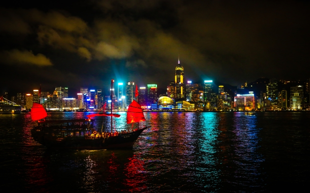 A classic Chinese junk carries tourists across the water as the daily light show adds colour to the cityscape.