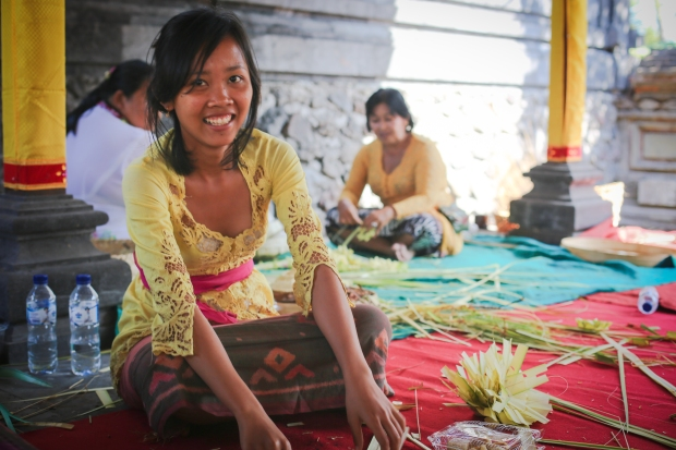 Young women weave decorations to form part of the equistite offerings for the upcoming Air Jeruk Temple ceremony.
